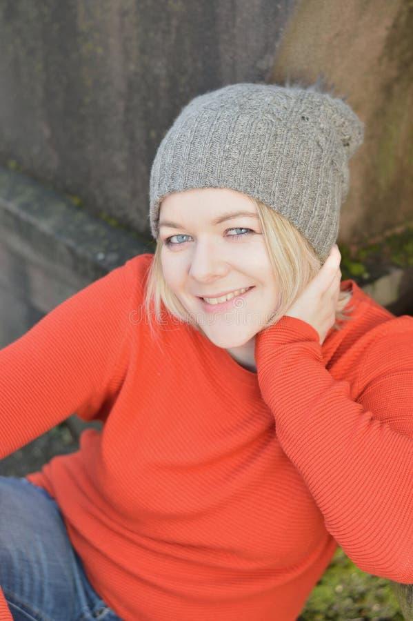 Mujer con el sombrero de punto que se sienta y que se inclina contra una piedra imagen de archivo