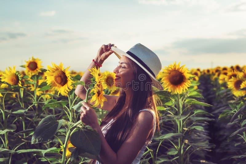 Mujer con el sombrero en un campo del girasol fotografía de archivo