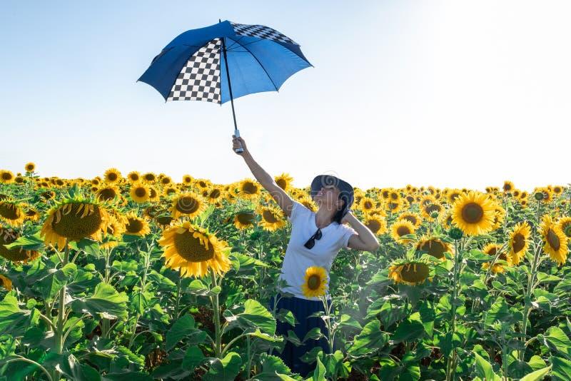 Mujer con el sombrero en un campo del girasol con el paraguas fotos de archivo libres de regalías