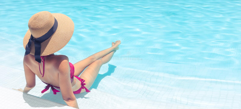 Mujer con el sombrero marrón que se relaja en piscina con agua azul en el sol, concepto del día de fiesta foto de archivo libre de regalías