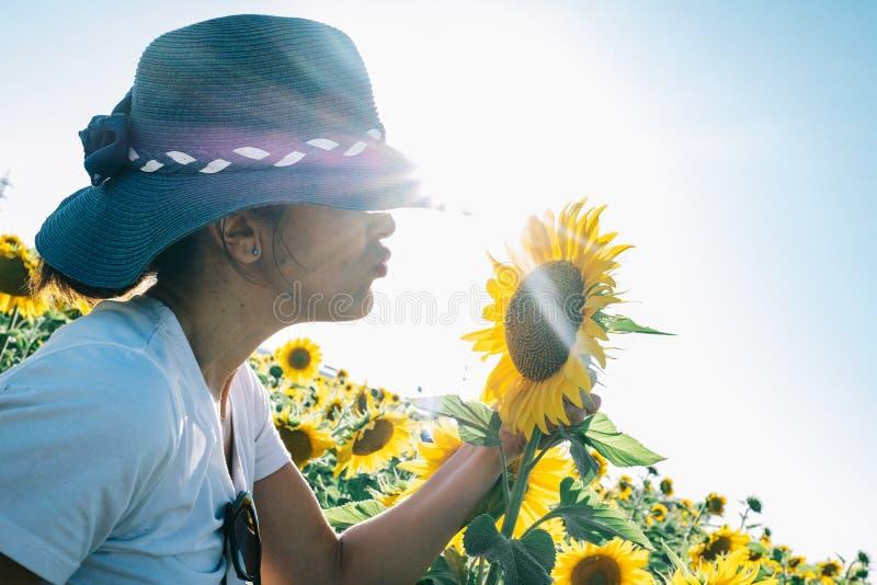 Mujer con el sombrero que besa una planta del girasol que le da el sol imágenes de archivo libres de regalías