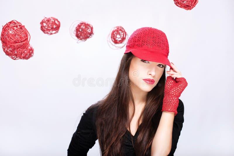Mujer con el sombrero rojo entre las bolas rojas fotografía de archivo libre de regalías