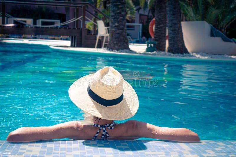 Mujer con el sunhat que se relaja en piscina en el balneario imágenes de archivo libres de regalías