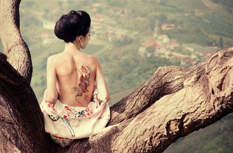 Mujer con el tatuaje de la serpiente en ella detrás imagen de archivo