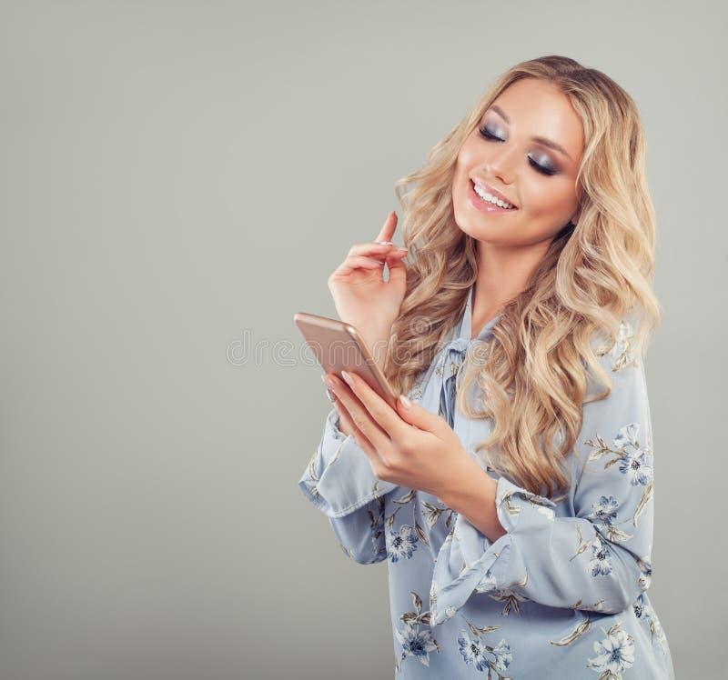 mujer con el teléfono celular Muchacha sonriente hermosa fotos de archivo libres de regalías