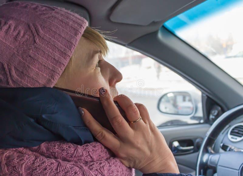 Mujer con el teléfono en el asiento del ` s del conductor en el coche fotos de archivo libres de regalías