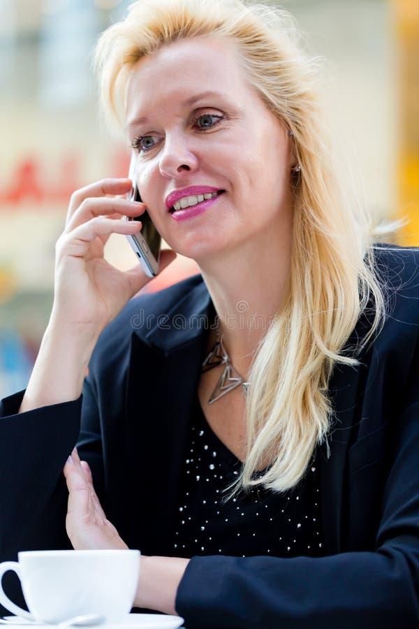 Mujer con el teléfono en café de consumición del café imagen de archivo libre de regalías