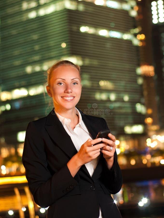 Mujer con el teléfono móvil en la ciudad grande fotografía de archivo libre de regalías