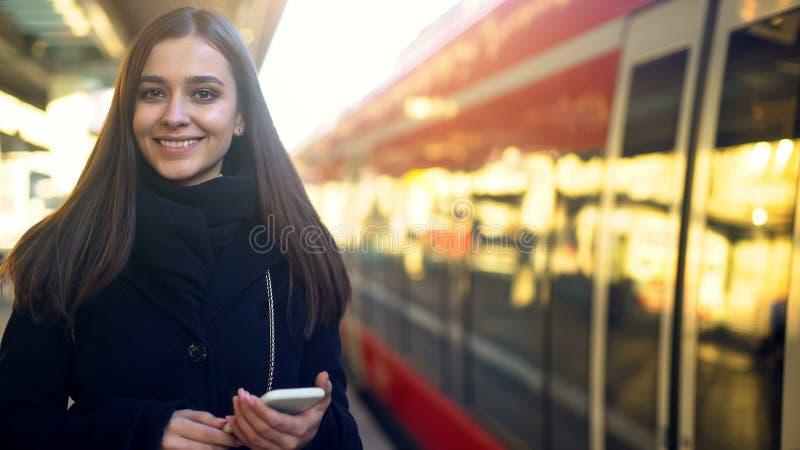 Mujer con el teléfono que sonríe cerca del tren, pago móvil rápido para la tecnología de los boletos fotografía de archivo libre de regalías
