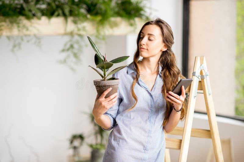 Mujer con el teléfono y la maceta foto de archivo libre de regalías