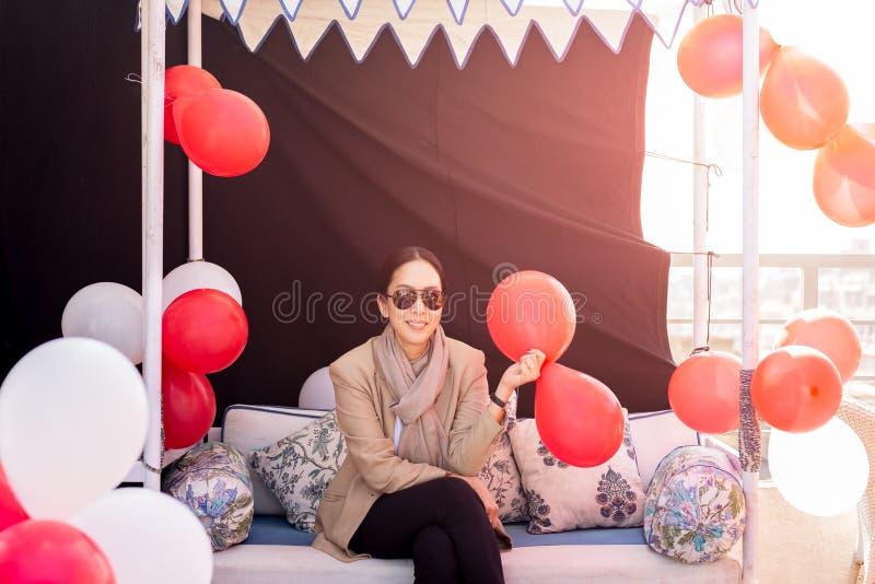 Mujer con el traje y la bufanda que se sientan en una mano del sofá que sostiene los globos rojos imagen de archivo libre de regalías