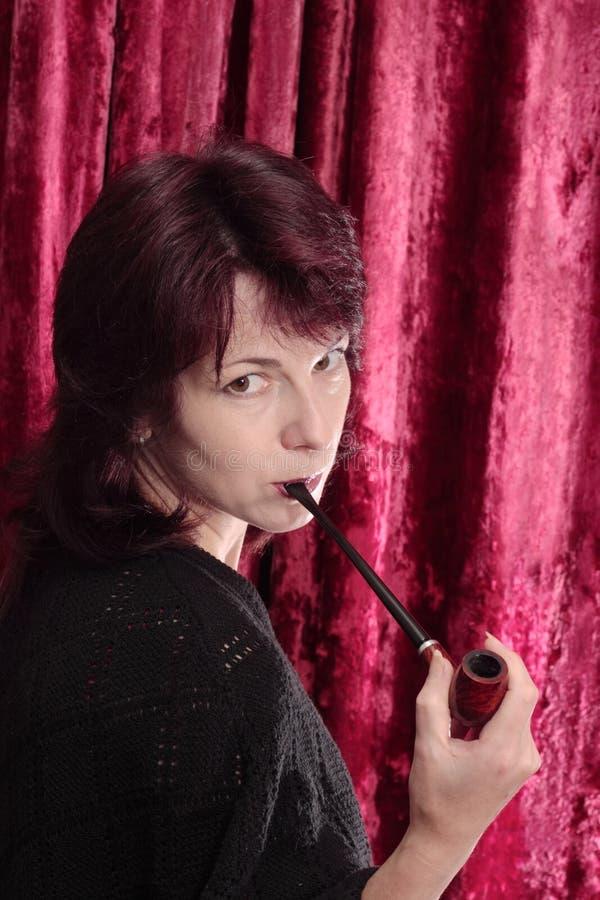 Mujer con el tubo de tabaco imagen de archivo