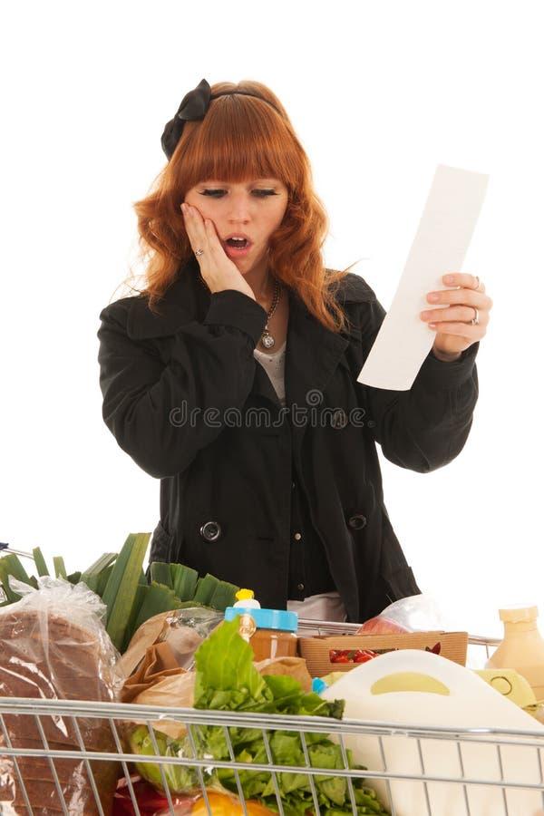 Mujer con el ultramarinos lleno de la lechería del carro de la compra que asusta por el recibo foto de archivo libre de regalías
