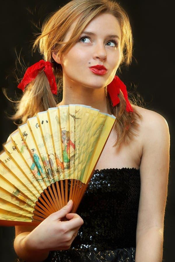Mujer con el ventilador imagenes de archivo