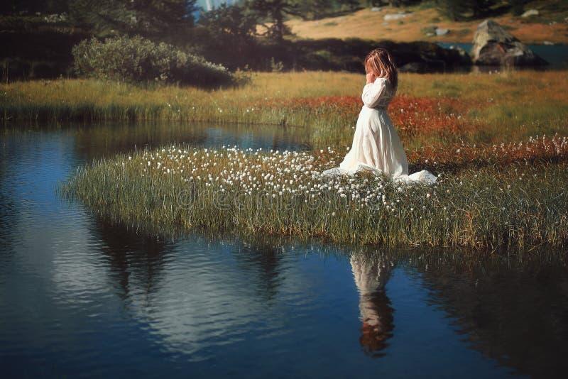 Mujer con el vestido del vintage en el lago alpino foto de archivo