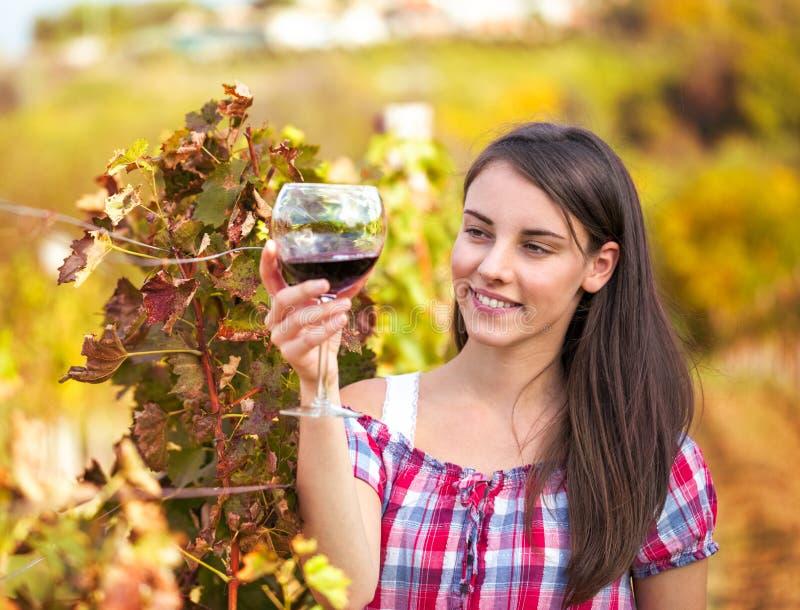 Mujer con el vidrio de vino en el viñedo. fotografía de archivo