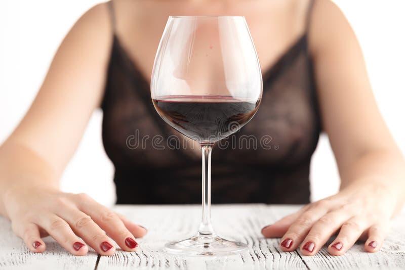 Mujer con el vidrio de vino rojo en fondo ligero imagenes de archivo