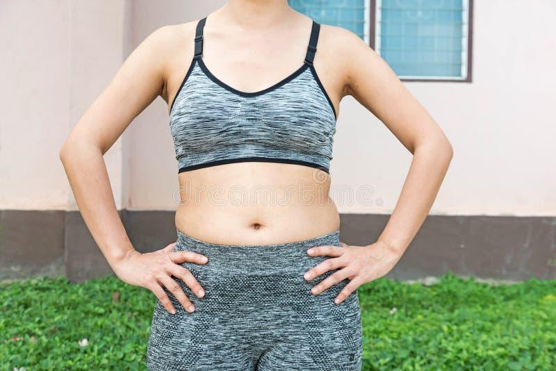 mujer con el vientre del cuerpo gordo y la ropa de deportes que lleva que se prepara para y imagenes de archivo