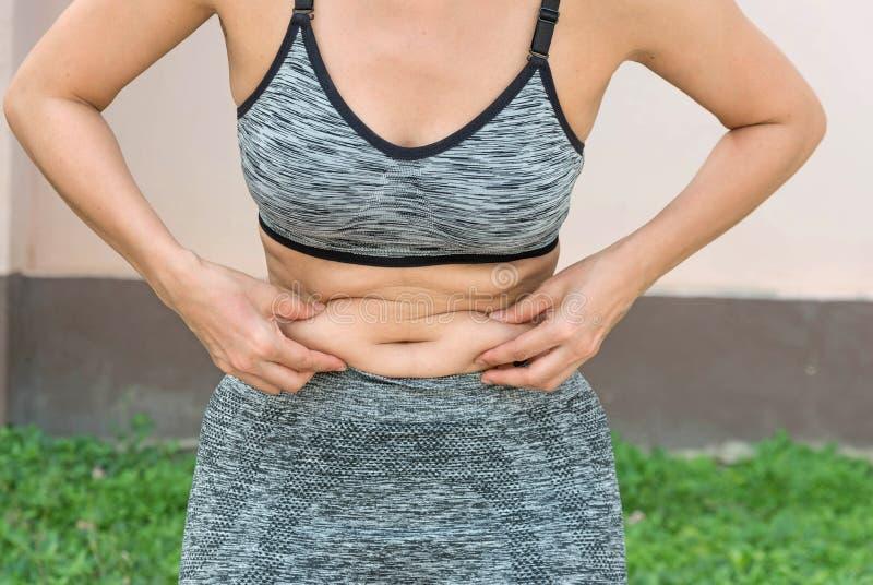 mujer con el vientre del cuerpo gordo y la ropa de deportes que lleva que se prepara para y imagen de archivo