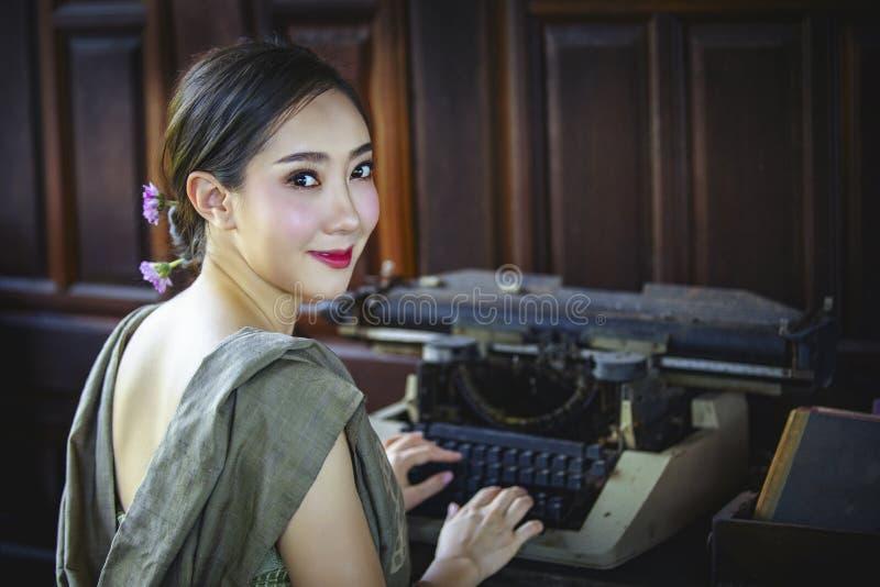 Mujer con el vintage de la máquina de escribir fotos de archivo libres de regalías