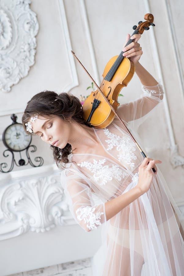 Mujer con el violín en el peignoir blanco boudoir seductive foto de archivo