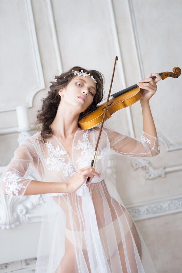 Mujer con el violín en el peignoir blanco boudoir seductive fotos de archivo