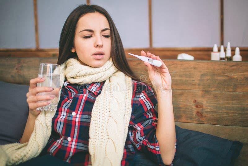 Mujer con el virus de la gripe que miente en cama, ella está midiendo su temperatura con un termómetro y está tocando su frente imagenes de archivo