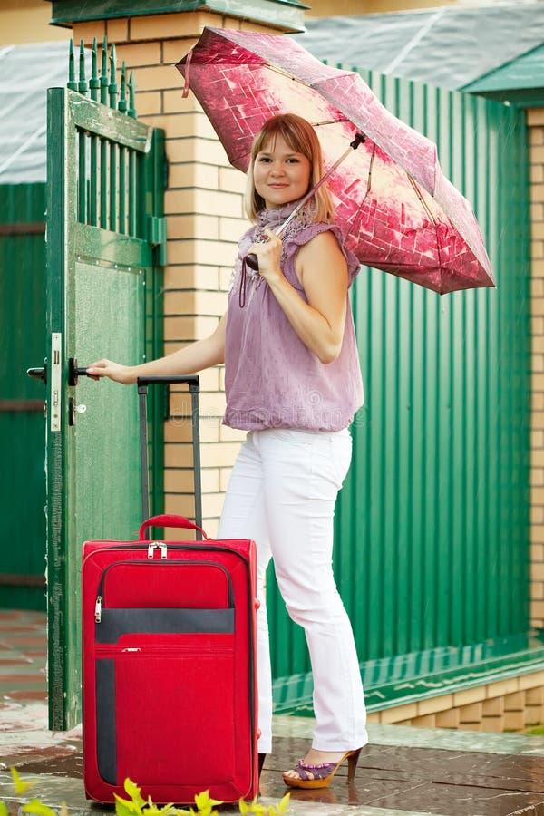 Mujer con equipaje cerca del hogar imagenes de archivo
