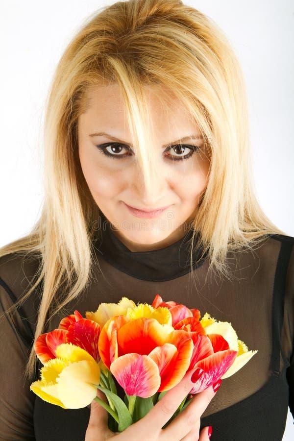 Mujer con estilo con los tulipanes rojos y amarillos fotos de archivo libres de regalías