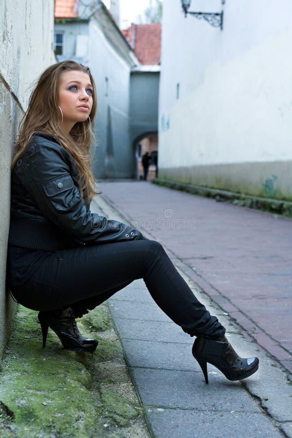 Mujer con estilo que se inclina en la pared fotografía de archivo