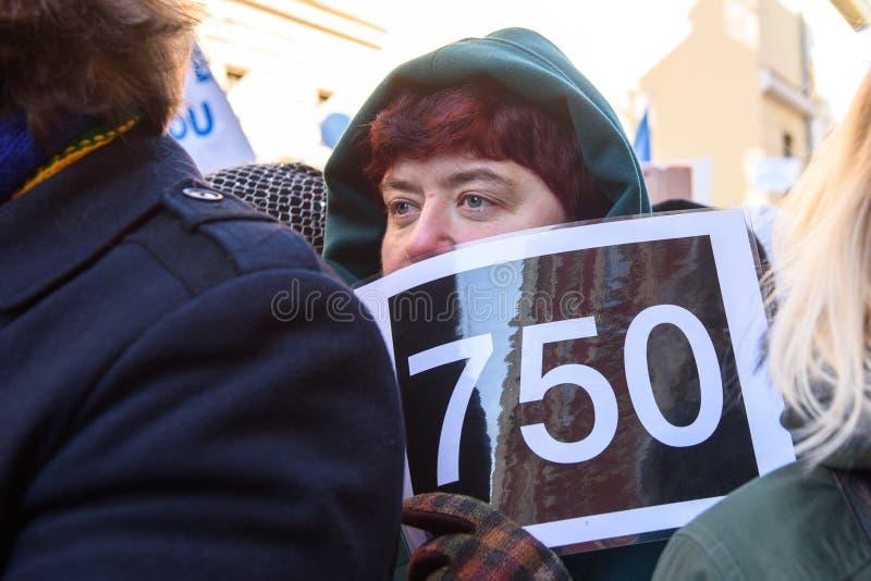 Mujer con 750 euros de la muestra en las manos, durante la protesta para pagar la subida profesores en Letonia fotografía de archivo
