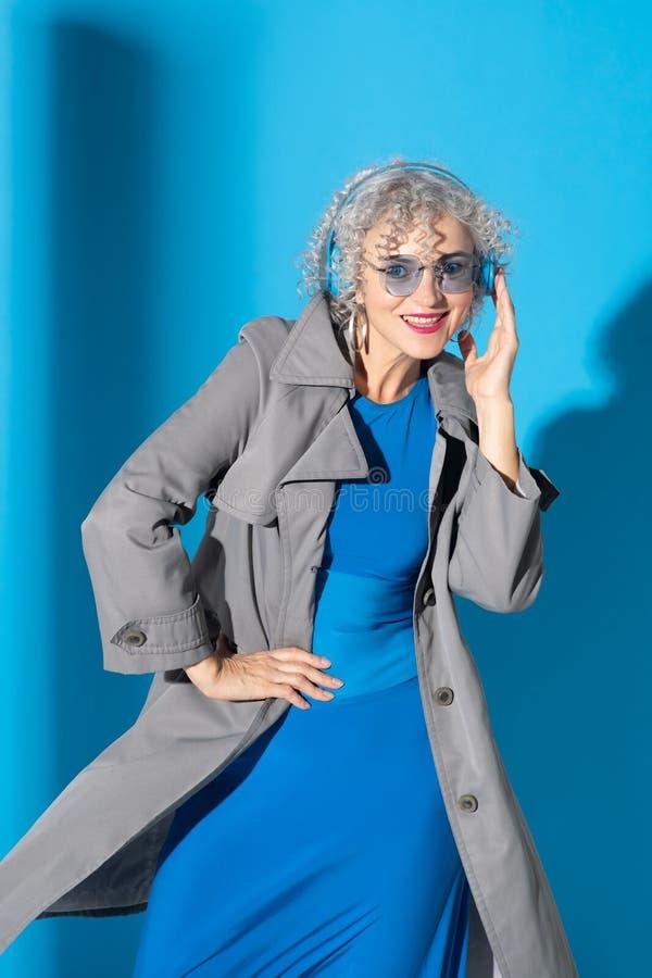 Mujer con gafas y auriculares posando cerca del fondo foto de archivo