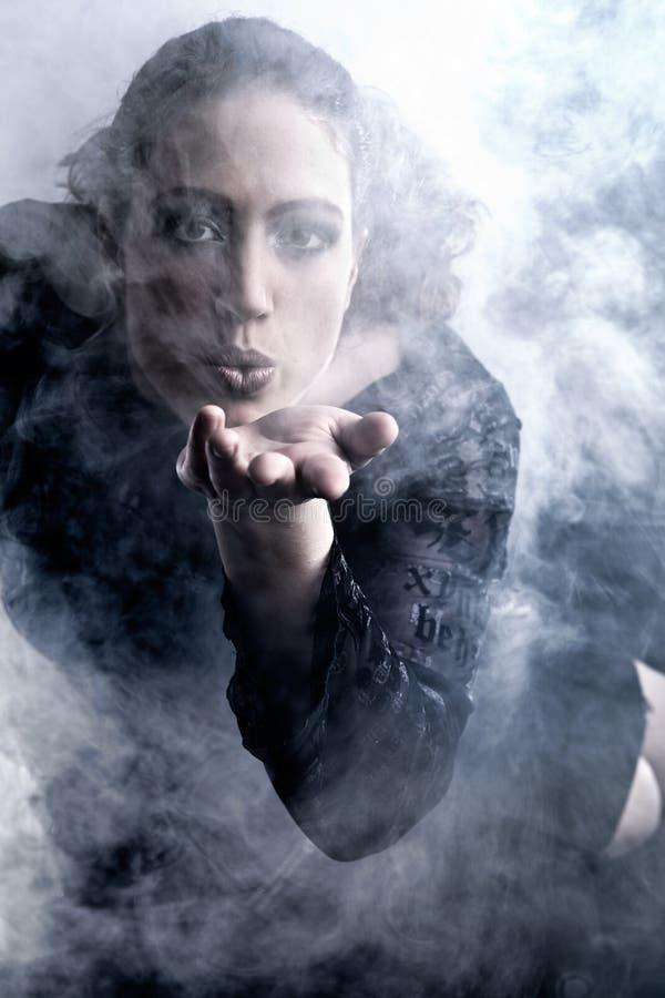 Mujer con humo que sopla largo del pelo rizado fotos de archivo