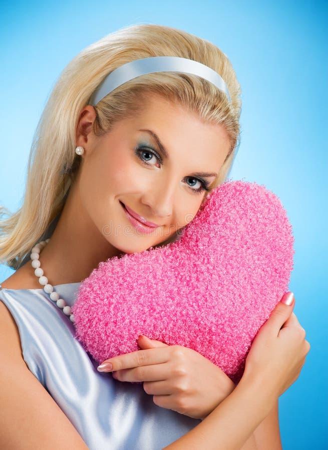 Mujer con la almohadilla mullida del corazón imagenes de archivo