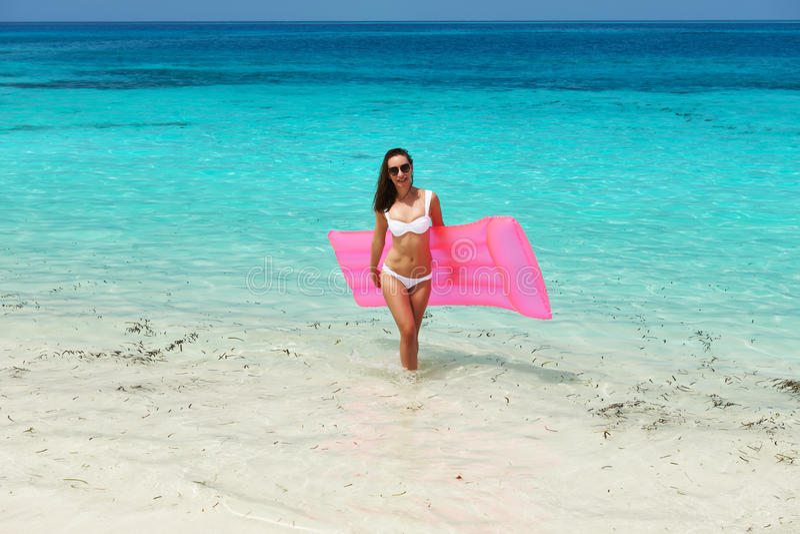 Mujer con la balsa inflable rosada en la playa imagen de archivo