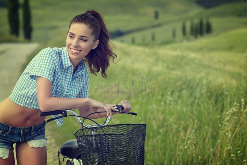 Mujer con la bici al aire libre, verano Toscana del vintage fotos de archivo