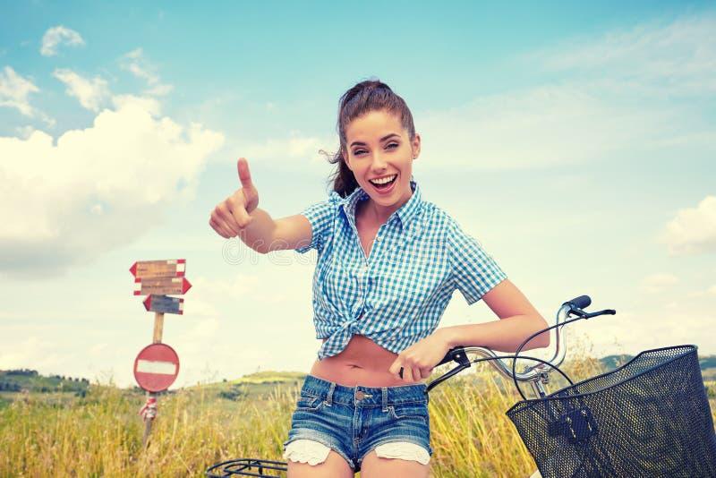 Mujer con la bici que se coloca en el camino y que mira a en alguna parte imágenes de archivo libres de regalías
