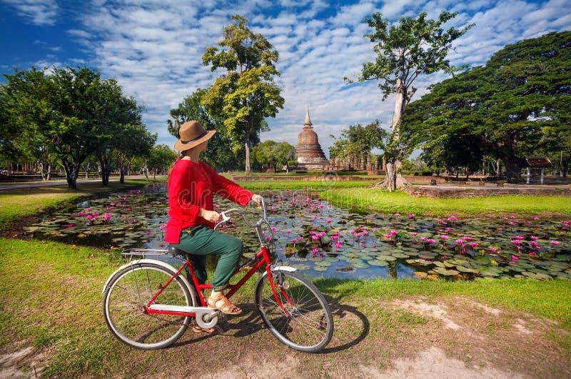 Mujer con la bicicleta cerca del templo en Tailandia fotografía de archivo