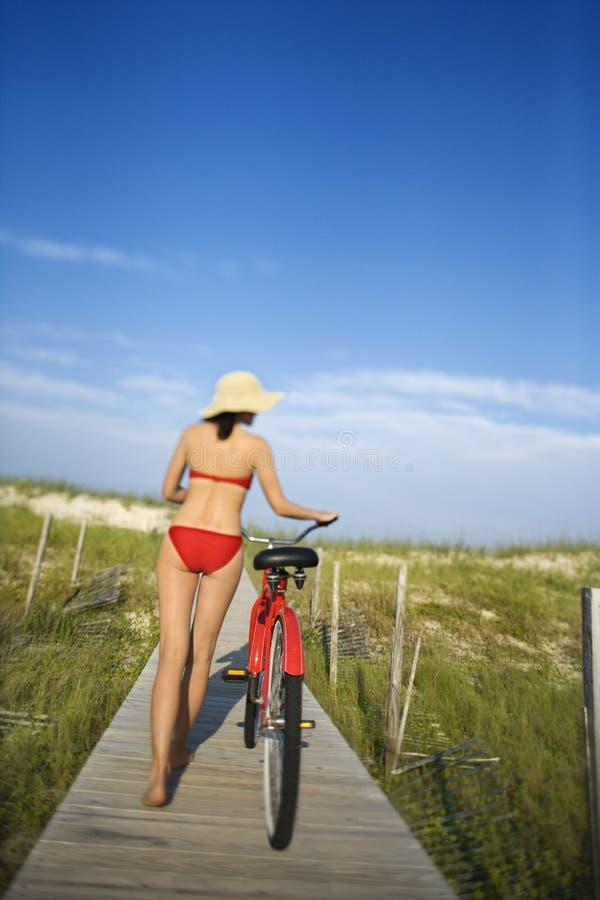 Mujer con la bicicleta en paseo marítimo imágenes de archivo libres de regalías