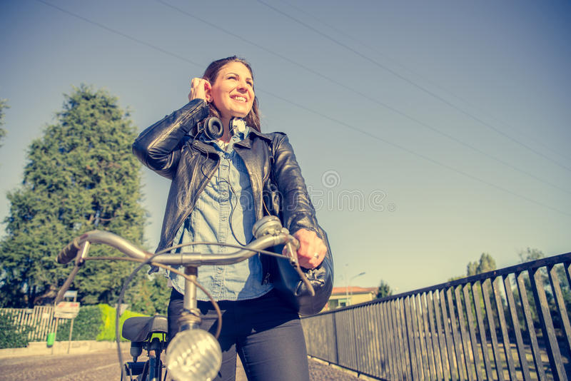 Mujer con la bicicleta que camina al aire libre imagen de archivo