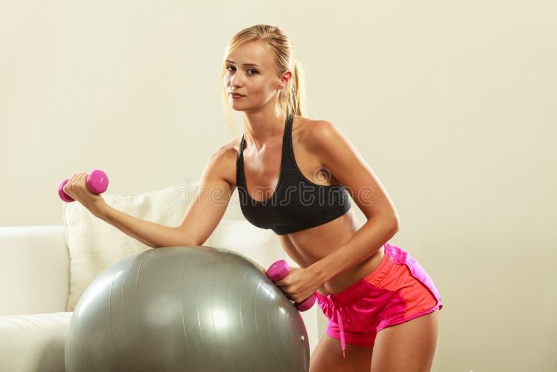 Mujer con la bola del gimnasio y pesa de gimnasia que hace ejercicio fotografía de archivo libre de regalías