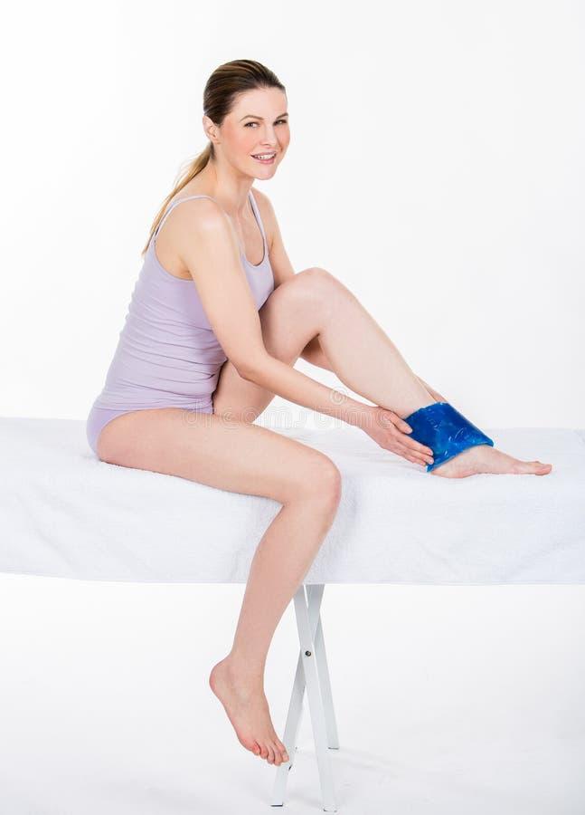Mujer con la bolsa de hielo en el tobillo foto de archivo