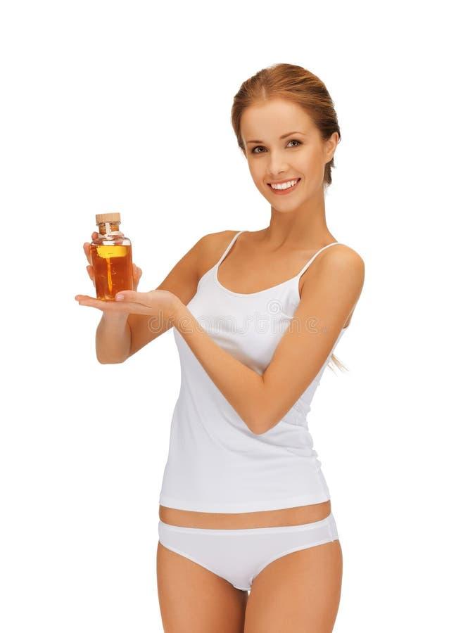 Mujer con la botella de aceite foto de archivo libre de regalías