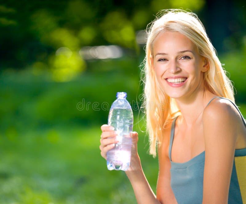Mujer con la botella de agua fotos de archivo