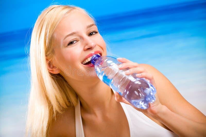 Mujer con la botella de agua imagen de archivo