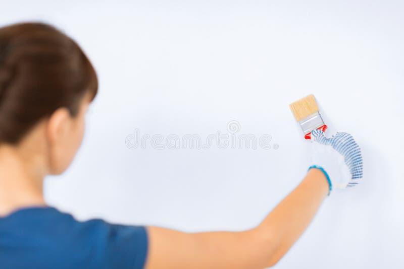Mujer con la brocha que colorea la pared imagen de archivo libre de regalías