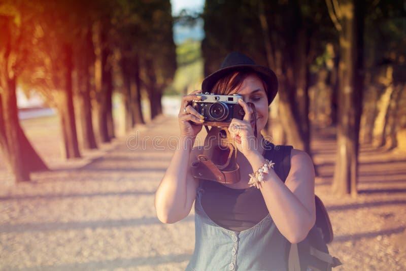 Mujer con la cámara del vintage en callejón del parque imagenes de archivo