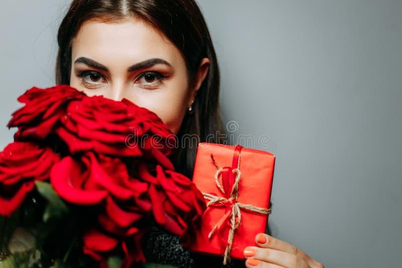 Mujer con la caja de regalo y el ramo rojos de rosas hermosas en gris, fotos de archivo libres de regalías