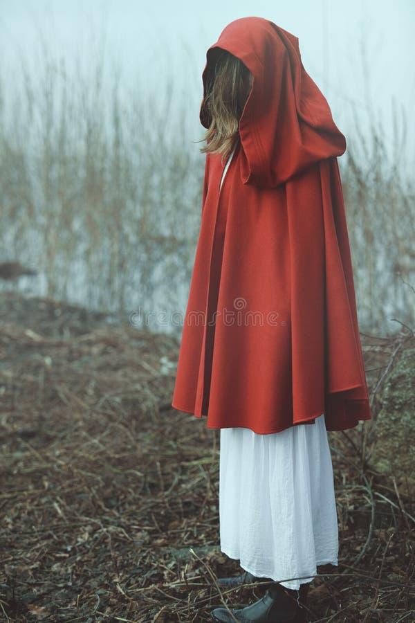 Mujer con la capa roja en tierra desolated brumosa imagen de archivo