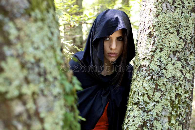 Mujer con la capilla en bosque de la fantasía foto de archivo